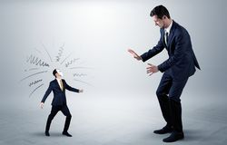 Conflict between small and big businessman. Conflict between small masked businessman and big elegant businessmann stock photos
