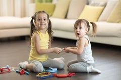 Conflict tussen kleine zusters De jonge geitjes vechten, neemt het peutermeisje stuk speelgoed, sibling verhoudingen royalty-vrije stock foto