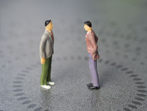 Conflict between two men. Concept image depicting a situation of a conflict or tension between two men. Miniature people - Copy space Stock Photo