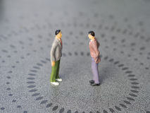 Conflict between two men. Concept image depicting a situation of a conflict or tension between two men. Miniature people - Copy space Royalty Free Stock Images
