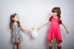 The conflict between two sisters. the kids are fighting, fight over for toy royalty free stock image