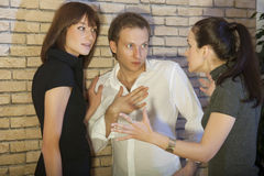 Conflict between two women and man. Conflict between friends - angry woman speaks to the couple Royalty Free Stock Images