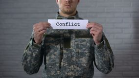 Conflict word written on sign in hands of soldier, military annexation, war. Stock footage stock footage