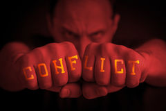 CONFLICT written on an angry man's fists. CONFLICT written on the fingers of an angry man's fists. Red colored. Message concept image Stock Photo