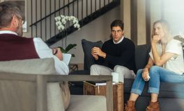Conflicted couple getting relationship counseling. Couple is sitting on sofa and talking to the psychologist while doctor is making notes. Conflicted husband and Stock Photography