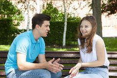 Conflicted couple not talking to each other seated on a wooden bench in park stock images