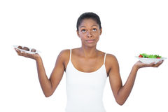 Conflicted woman deciding to eat healthily or not. On white background Royalty Free Stock Photos