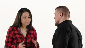 Conflicting couple quarrels and shouts isolated on white background. Man and woman quarreling, find out the relationship, making hand gestures, the woman grabs stock video footage