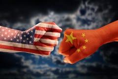 Conflicto comercial, puños con las banderas de los E.E.U.U. y China contra el ea imagenes de archivo