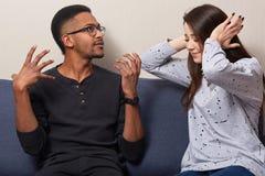 Conflicto de la familia multiétnica La mujer desesperada cubre ambos oídos, ignora la explicación de los maridos o gritando, pres foto de archivo