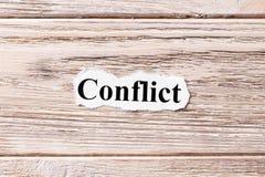 Conflicto de la palabra en el papel Concepto Palabras del conflicto en un fondo de madera fotografía de archivo libre de regalías
