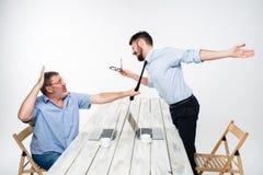 Conflicto del negocio Los dos hombres que expresan negatividad mientras que un hombre que ase la corbata de su opositor Fotos de archivo