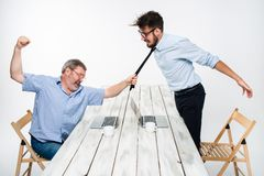 Conflit d'affaires Les deux hommes exprimant la négativité tandis qu'un homme saisissant la cravate de son adversaire Image libre de droits