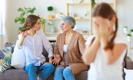 Conflito de gerações mãe irritada e avó da família três que discutem a criança impertinente foto de stock