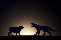 Conflito do conceito Carneiros contra a silhueta do lobo imagem de stock royalty free