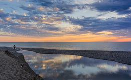 The confluence of river and sea. The confluence of the river and the sea under a beautiful sunset sky Stock Images