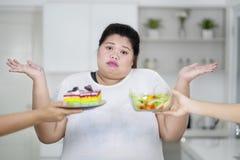 Confonda la donna di peso eccessivo non conosce che cosa scegliere fra il dolce dell'arcobaleno e l'insalata immagini stock libere da diritti