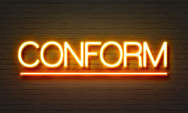 Conform neon sign on brick wall background. Stock Image