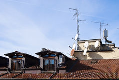 Conformism. Television satellite dishes on the roof of an old building Stock Photos