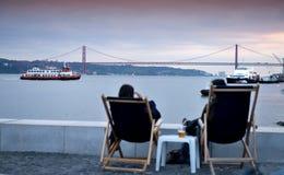 Confort sur la chaise de plate-forme - bord de mer de la baie de Tajo à Lisbonne Photo libre de droits