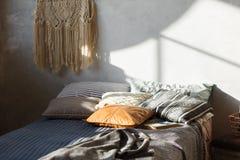 Conforte el interior del dormitorio del desván con la cama en color gris Muro de cemento en fondo Imagen de archivo libre de regalías