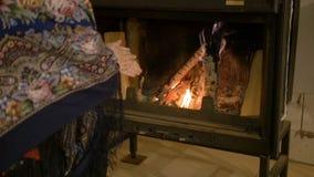 Conforto home Mulher que aquece suas mãos pelo fogo Aqueça no inverno vídeos de arquivo