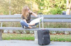 Confounded, lost or thinking tourist woman looking at map for right way. Sitting on the bench in the park, luggage on the street stock images