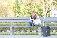 Confounded, lost or thinking tourist woman looking at map for right way. Sitting on the bench in the park, luggage on the street stock photos