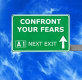 CONFRONT YOUR FEARS road sign against clear blue sky royalty free stock images