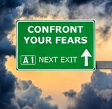 CONFRONT YOUR FEARS road sign against clear blue sky stock photography