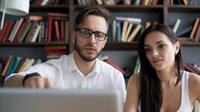 Confrontando le idee il lavoro vicino discuta con il desktop in sottotetto video d archivio