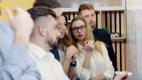 Confrontando le idee nell'ufficio I colleghi discutono il problema e fanno le note su un bordo bianco stock footage