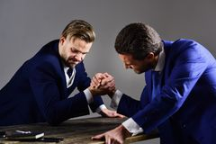 Confrontation of business leaders. Winner and defeated concept. Men in suit or businessmen with aggressive faces compete in armwrestling on table on dark Stock Photography
