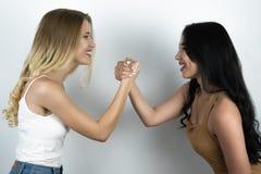Confrontation positive entre la blonde et le fond blanc de brune photo stock