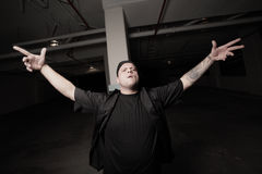 Confrontational man in a dark garage. Young man in a dark garage expressing anger Stock Image