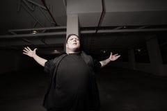 Confrontational man in a dark garage. Young man in a dark garage expressing anger Stock Photos