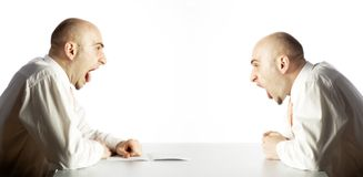 Confrontational yelling. Two men sit opposite each other at a table with their mouths wide open, appearing to be yelling at one another at the top of their Royalty Free Stock Photo