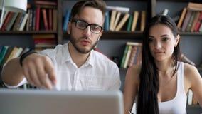 Confronti le idee il lavoro vicino discutono con il desktop in sottotetto video d archivio