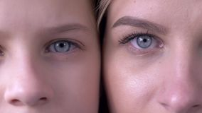 Confronto di età, occhi della madre caucasica e figlia accanto ad una un altro che esamina insieme la macchina fotografica