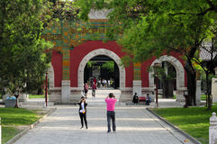 Confucius Temple Beijing China. Chinese tourists taking pictures near the glazed memorial arch at the Confucius Temple property in Beijing China Stock Photo