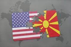 confunda com a bandeira nacional de Estados Unidos da América e de Macedônia em um fundo do mapa do mundo fotografia de stock