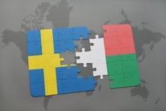 confunda com a bandeira nacional de sweden e de madagascar em um fundo do mapa do mundo Fotografia de Stock Royalty Free