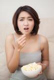 Confunda a las mujeres hermosas que comen las palomitas Imágenes de archivo libres de regalías