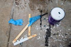 Confusão de pintura - uma lata da pintura branca senta-se no pano de forro desarrumado com a pintura branca e preta cercada por v foto de stock