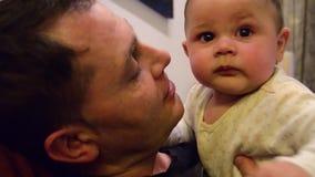 Confus six mois de bébé garçon faisant le visage drôle quand essai de papa pour le secouer et pour chatouiller le sien de ret clips vidéos