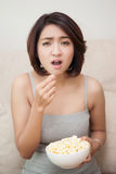 Confuse beautiful women eating popcorn Royalty Free Stock Images