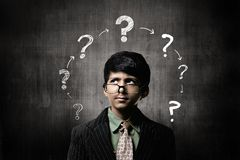 Confuse Little Boy Wearing Glasses, Thinking Near Chalkboard royalty free stock images