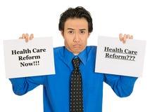 Confused бизнесмен держа знак реформы здравоохранения озадаченный Стоковые Изображения RF