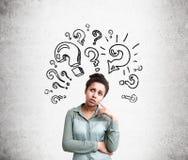 Confused женщина с вопросами Стоковые Изображения