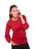 Confused испанская дама говоря на ее телефоне Стоковые Фотографии RF